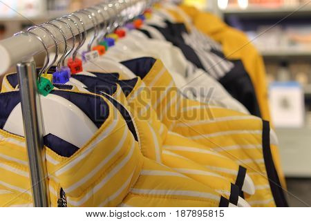 Row of yellow and blue jackets on a store hanging rail showing size markers for EU clothes sizes