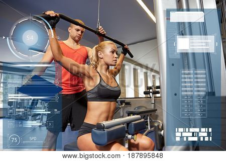 sport, fitness, exercising and people concept - young woman flexing muscles on gym machine and personal trainer with clipboard over virtual charts