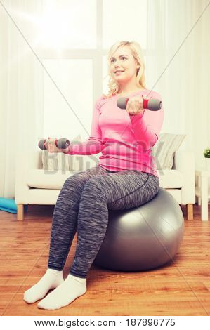 fitness, sport, training and lifestyle concept - smiling woman with dumbbells and fit ball exercising at home
