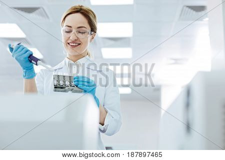 Keep smiling. Attractive woman keeping medicine dropper in right hand while looking downwards and controlling the process