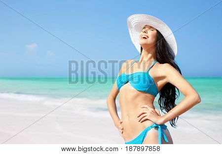 summer holidays, vacation, travel and people concept - smiling young woman in bikini swimsuit and sun hat on beach over sea and blue sky background