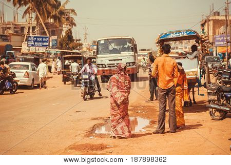 KARNATAKA, INDIA - FEB 10, 2017: Street of an indian city with drivers passengers bikes and transport traffic outdoor on February 10, 2017. Population of Karnataka state is 62000000 people