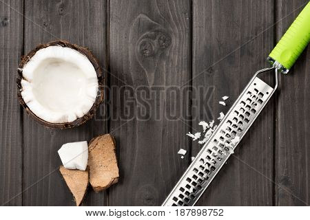Top View Of Coconut Pieces With Grater On Wooden Background, Coconut Shavings