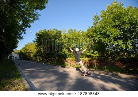 A young man in a helmet and protective gloves makes a stand-up slide on a longboard in the resort area of the city