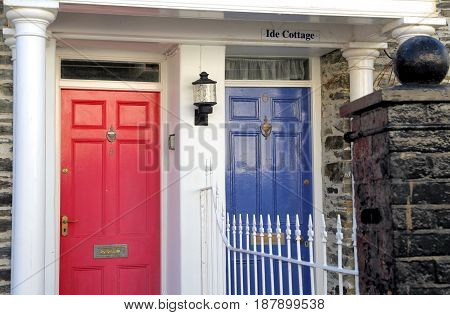 Red and blue Georgian style wooden doors with white pillars and white railings with black stone ball on brick pillar