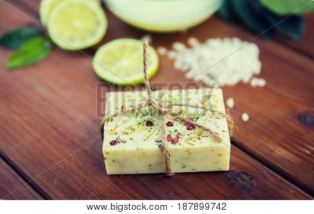beauty, spa, body care, bath and natural cosmetics concept - close up of handmade herbal soap bar on wooden table
