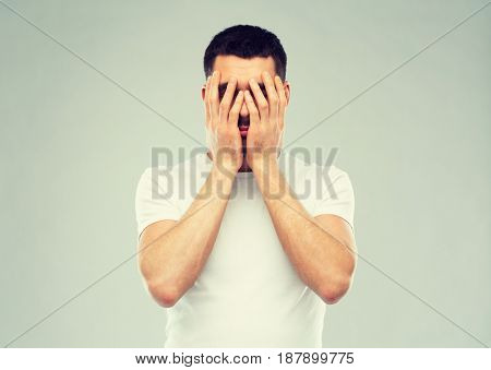 people, crisis, emotions and stress concept - man in white t-shirt covering his face with hands over gray background