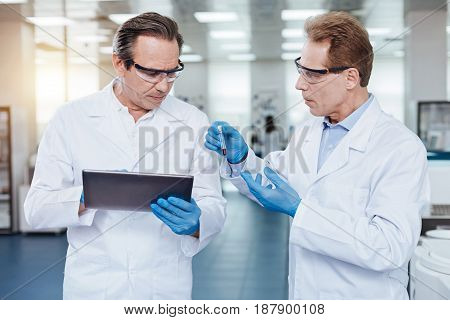What is it. Serious practitioner wearing protective glasses wrinkling forehead while using tablet