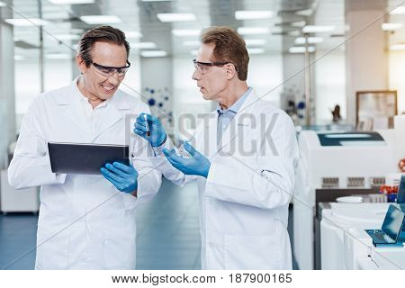 Listen to me. Worried lab assistant standing in semi position and showing test-tube with blood to his colleague while explaining the problem to him