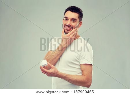beauty, skin care, body care and people concept - smiling young man applying cream to face over gray background