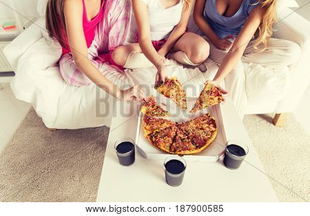 friendship, people, pajama party and junk food concept - close up of friends or teenage girls eating pizza at home