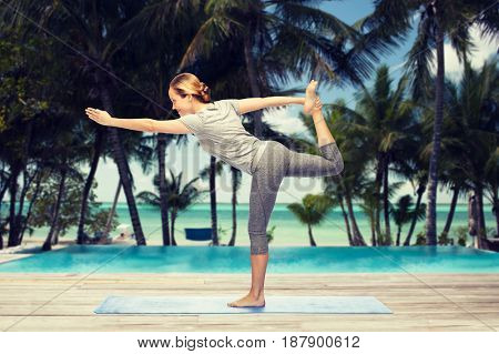 fitness, sport, people and healthy lifestyle concept - woman making yoga in lord of the dance pose on mat over hotel resort pool on tropical beach background