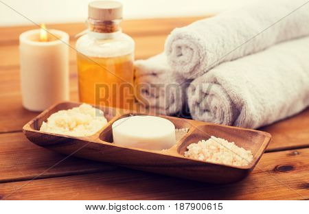 beauty, spa, body care, natural cosmetics and bath concept - close up of soap natural cosmeticshimalayan salt and scrub in wooden bowl on table