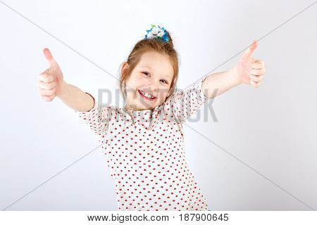 Girl schoolgirl with widely separated, raised hands and thumbs up