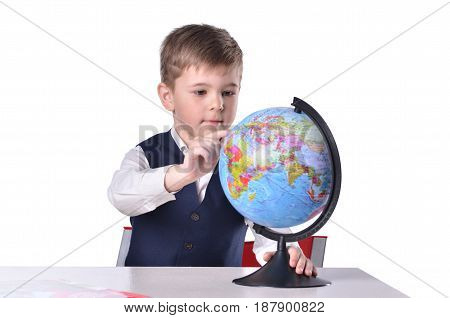 Schoolboy at the desk searching something on a globe of world isolated on white background