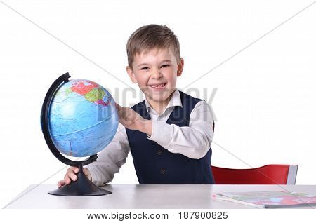 Schoolboy at the desk laughs and pointing on a globe isolated on white background