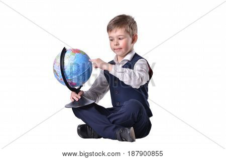 Sitting schoolboy pointing on a globe of world isolated on white background