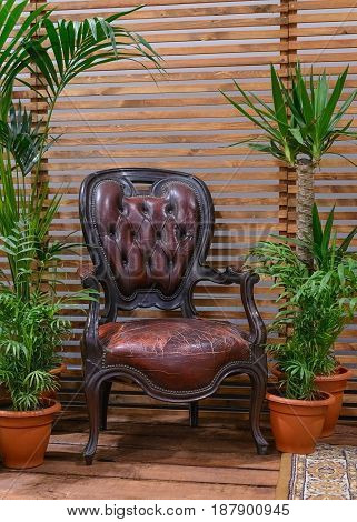 antique leather chair on a wooden veranda