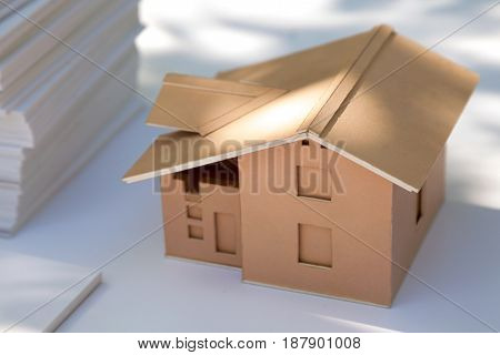 Small cardboard house model on white. New home design for sale. Abstract cardboard real estate miniature in the sunlight