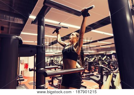 sport, fitness, lifestyle and people concept - woman exercising and doing pull-ups in gym