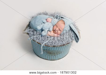 kid dressed as rabbit sleeping with blue toy