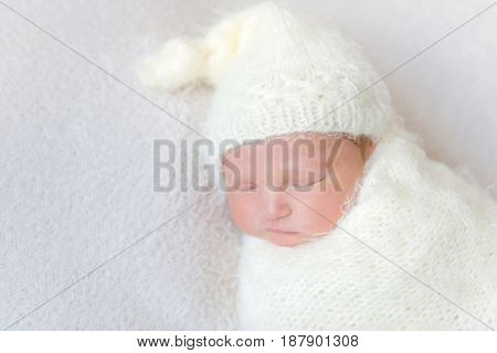 infant wearing a warm white hat sleeping, closeup