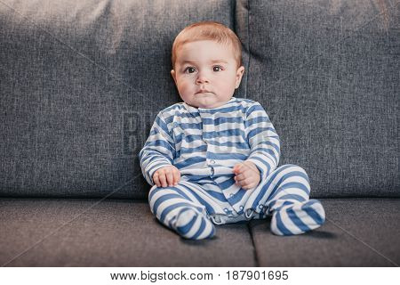 Front View Of Adorable Baby Boy Sitting On Sofa And Looking At Camera
