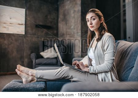 Portrait Of Woman Typing On Laptop And Relaxing On Sofa At Home. Home Business Concept