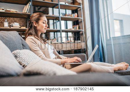 Side View Of Woman Working On Laptop While Relaxing On Sofa At Home