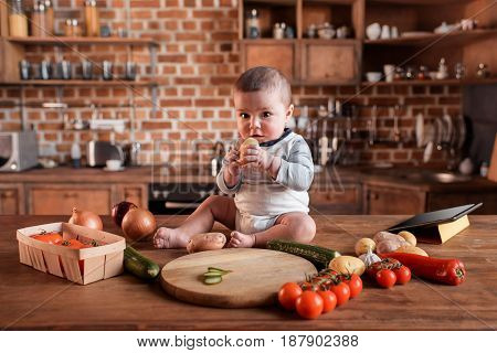 Little Boy Sitting On Kitchen Table Around Of Raw Vegetables Before Cooking A Dinner