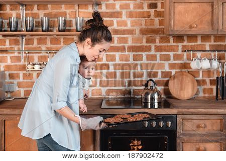 Side view of young woman with her son baking cookies in the kitchen