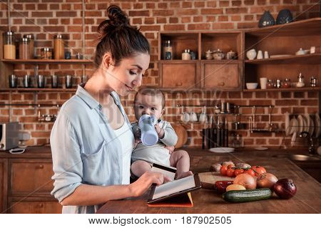 Portrait Of Mother And Baby Boy Shopping Online With Digital Tablet And Credit Card