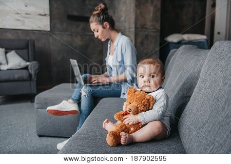 Adorable Little Boy With Teddy Bear Toy Sitting On Couch While His Mother Working On Laptop At Home.