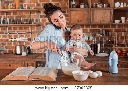 Young Mother Holding Her Son, Talking On Smartphone And Mixing A Dough At The Kitchen. Family Life A