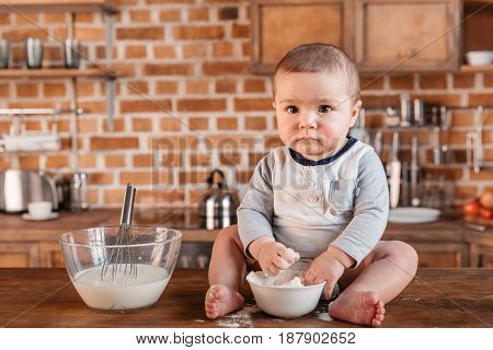 Adorable Little Boy Looking At Camera While Playing With Flour And Sitting On Kitchen Table. Domesti