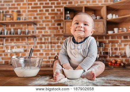 Happy Little Boy Playing With Flour And Sitting On Kitchen Table. Domestic Life Concept
