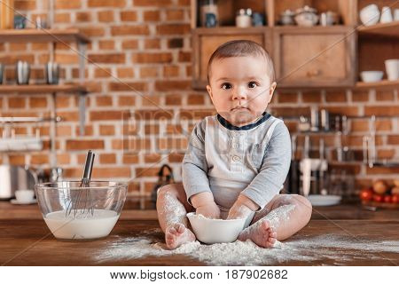 Portrait Of  Little Boy Playing With Flour And Sitting On Kitchen Table. Domestic Life Concept