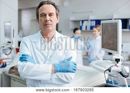 Competent man. Gray-haired practitioner pressing lips and looking straight at camera while standing isolated on lab background