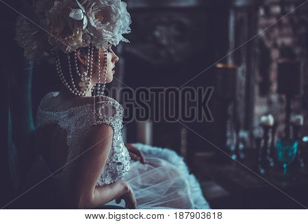 Beautiful bride sits on a chair. Luxury palace.