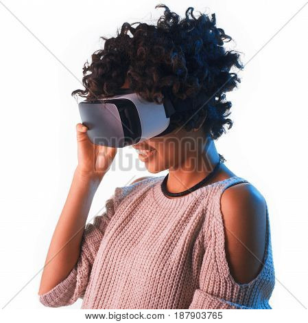 Smiling young African woman adjusting the VR headset isolated on white.
