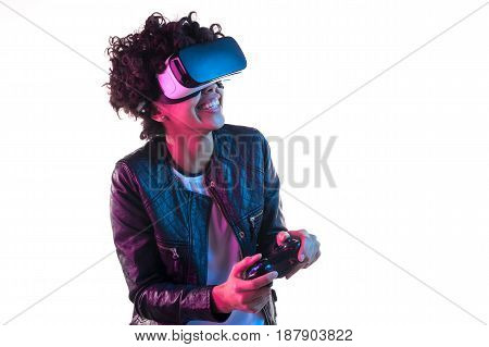 Excited woman isolated on white holding a gamepad and playing the VR game.