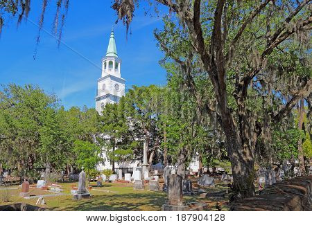 Spire main building and graveyard framed by Spanish moss-covered trees at the parish church of St. Helena in the historic district of downtown Beaufort South Carolina
