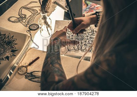Yong woman painting calligraphic ornament at table in salon. She turning back to camera. Picture tattoo concept