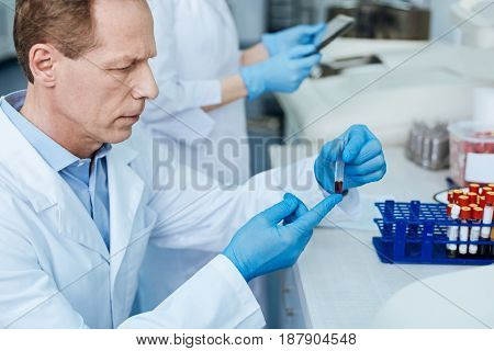 Blood test. Profile photo of competent practitioner while holding test glass with blood and going to test it while sitting in the lab
