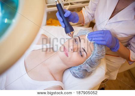 doctor cosmetologist doing facial massage girl Spa medical device