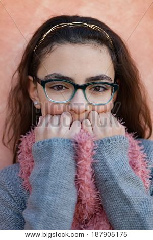 Smiling preteen girl wearing pink scarf and glasses