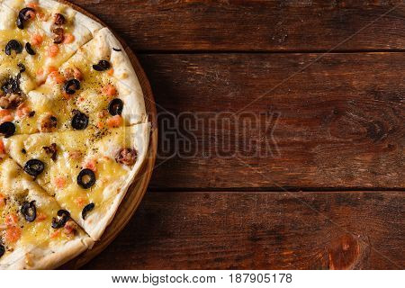 Appetizing fresh italian pizza with shrimps, olives and cheese served on rustic wooden table. Dark background with free space for text.