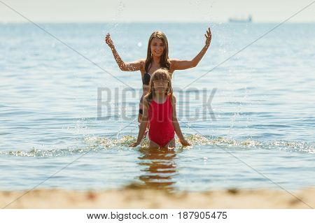Little girl child and mother having fun in ocean. Kid and woman bathing in sea splashing water. Summer vacation holiday relax.