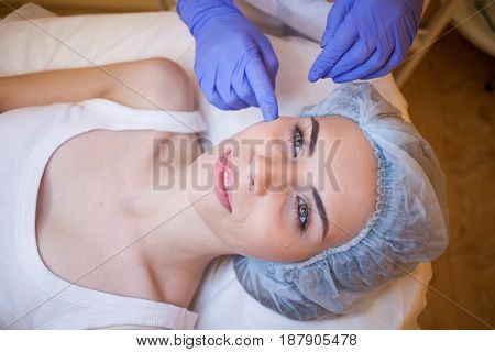 doctor cosmetologist shows on cheek face patient Spa