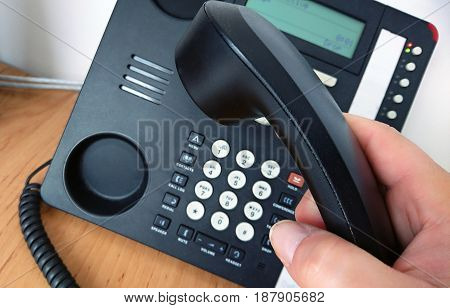 Close-up of picking telephone handset up for making a call.